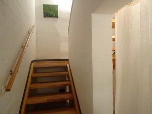 eine sehr flache Holztreppe führt zu den einzelnen Zimmern